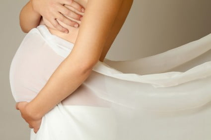 Pregnant woman in a white tulle